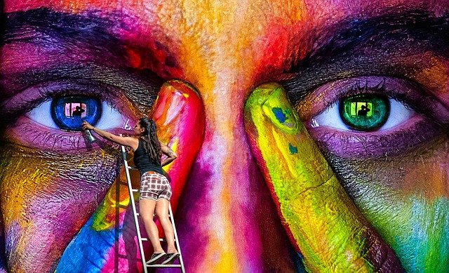 A girl painting a face on the dec using multiple colors